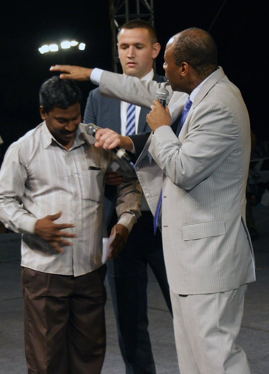 This man couldn't lift his hand before the prayer, and now he can. God healed him!