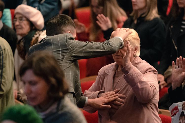 Во время молитвы другие пасторы и лидеры ходили по залу и возлагали руки на людей, которые нуждались в исцелении.